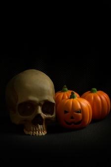 La presa ed il cranio della zucca di halloween nell'immagine di priorità bassa nera di festa.