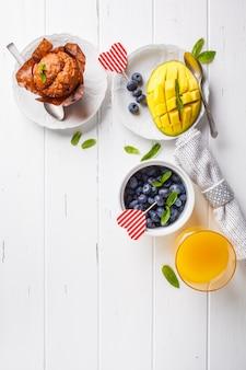 La prima colazione a san valentino servito con muffin, succhi, bacche e frutta, vista dall'alto, sfondo bianco.