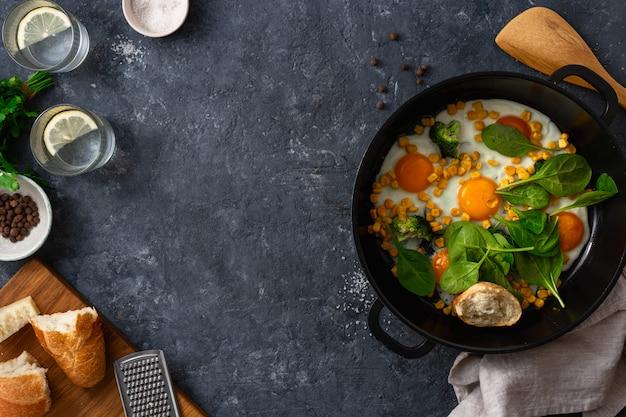 La prima colazione sana eggs la vista superiore su fondo di pietra scuro con copyspace
