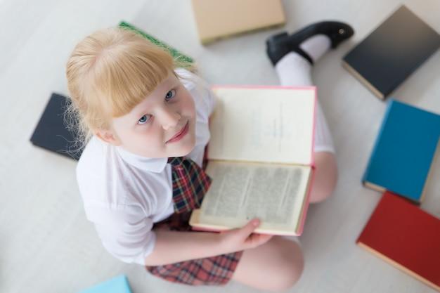 La prima elementare è seduta sul pavimento con i libri