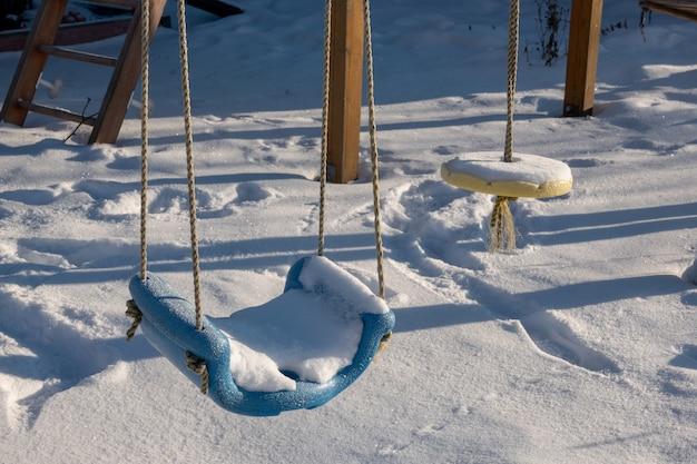 La prima neve è caduta sull'altalena dei bambini coperta di neve fresca sul sito