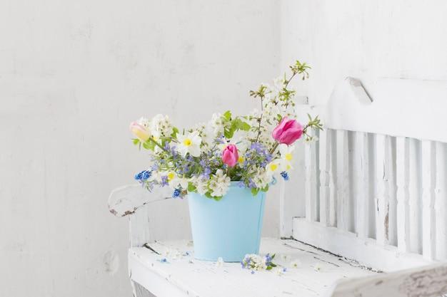 La primavera fiorisce nell'interno bianco d'annata con il vecchio banco di legno