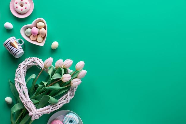La primavera geometrica piatta giaceva in bianco e verde sulla parete rosa pasqua, festa della mamma, compleanno di primavera o anniversario. pannello termico in plastica, uova di pasqua, caffettiera, tazze, tulipani, regali.