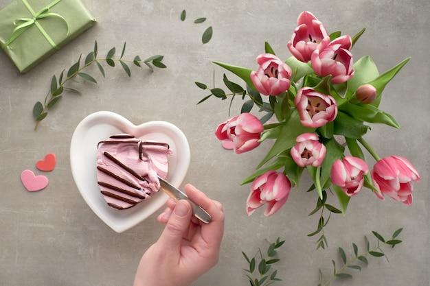 La primavera piatta giaceva con un mazzo di tulipani rosa, foglie di eucalipto