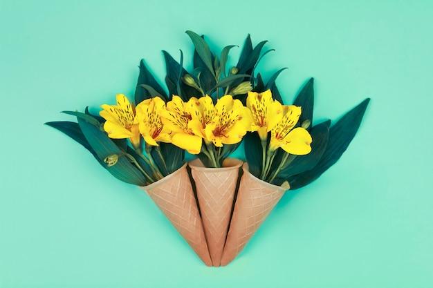 La primavera sta arrivando. mazzo di fiori gialli con foglie verdi in coni di cialda