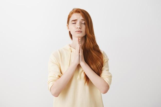 La promettente ragazza rossa preoccupata si tiene per mano in segno di supplica, pregando
