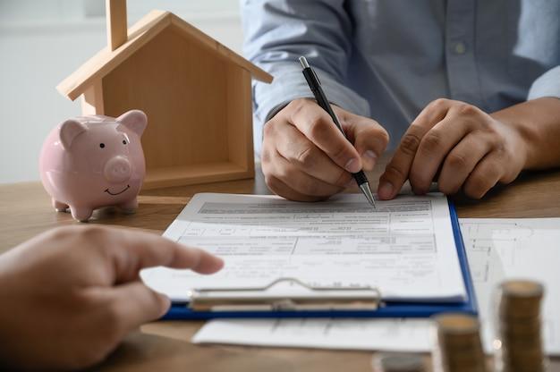 La proprietà della casa gli uomini d'affari che negoziano un contratto qui è dove è necessario firmare