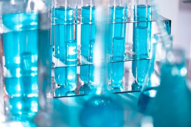 La provetta di vetro trabocca di nuovi condotti liquidi blu di soluzione liquida