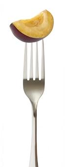 La prugna prugne ha tagliato un pezzo singolo sopra impalato una forchetta isolata