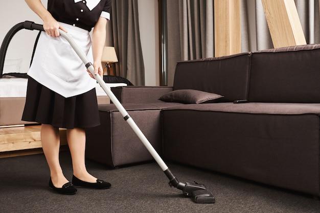La pulizia della casa è la chiave per la produttività. colpo ritagliato di cameriera durante il lavoro, pulizia del soggiorno con aspirapolvere, rimozione di sporcizia e pasticcio vicino al divano. la cameriera è pronta a far brillare questo posto