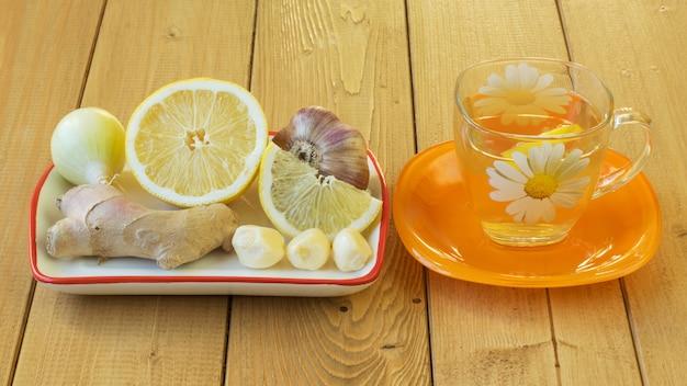 La radice di zenzero e miele sul tavolo di legno.
