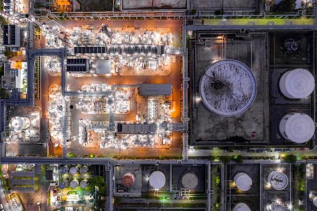 La raffineria di petrolio di vista aerea e la pianta di raffineria del gas formano la zona di industria alla notte.