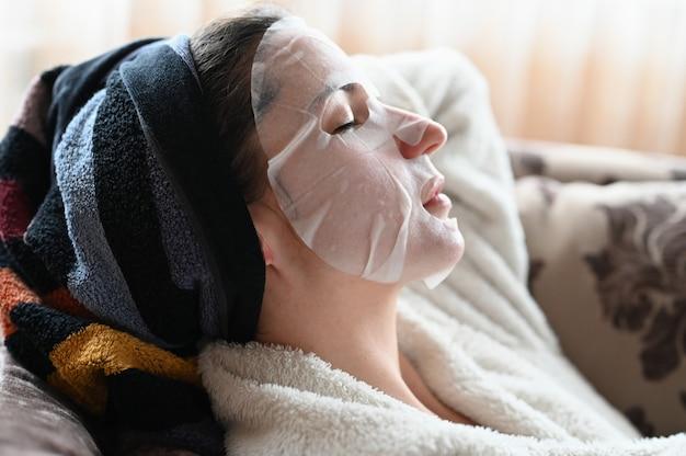 La ragazza a casa idrata la pelle del viso