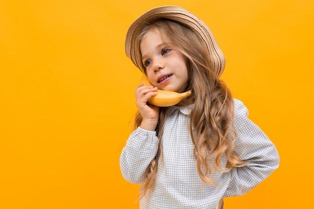 La ragazza abbastanza caucasica con il cappello tiene gesticola con la banana sulla parete gialla
