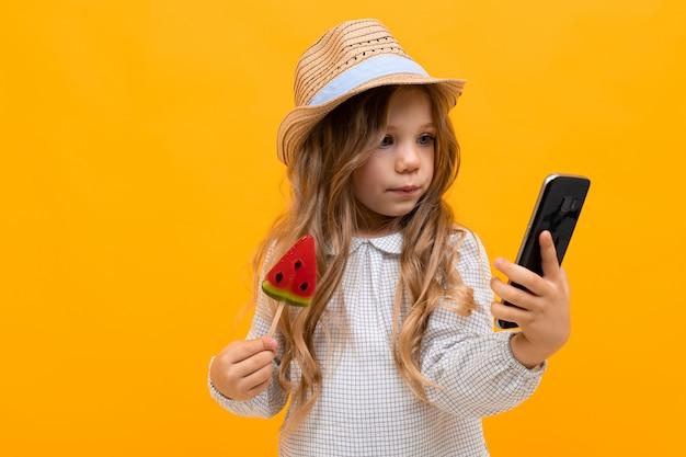 La ragazza abbastanza caucasica con il cappello tiene il lolipop e il telefono dell'anguria sulla parete gialla