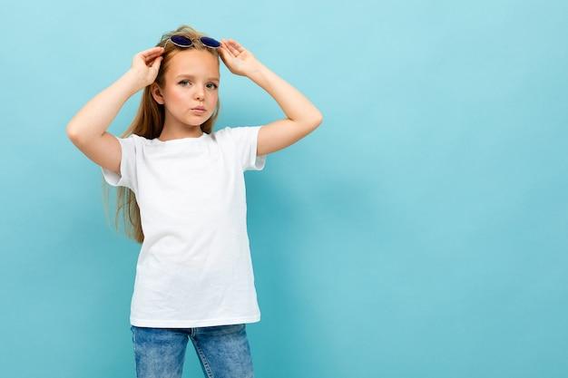 La ragazza abbastanza caucasica dell'adolescente con capelli marroni in rivestimento nero giudica gli occhiali da sole isolati su fondo blu