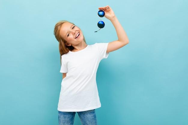 La ragazza abbastanza caucasica dell'adolescente con capelli marroni in rivestimento nero giudica gli occhiali da sole isolati sul blu