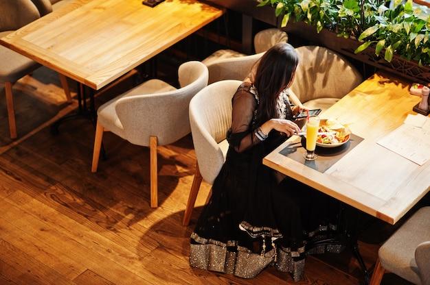 La ragazza abbastanza indiana in vestito nero dal saree ha posato al ristorante, sedendosi alla tavola con succo e insalata. guardando il cellulare.