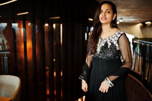 La ragazza abbastanza indiana in vestito nero dal saree ha proposto al ristorante.