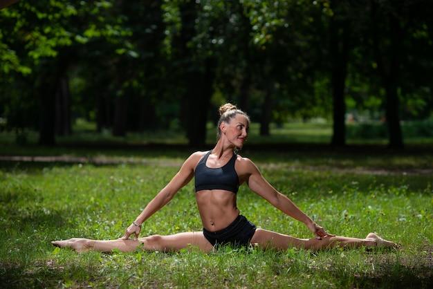 La ragazza acrobata esegue l'elemento acrobatico sull'erba nel parco