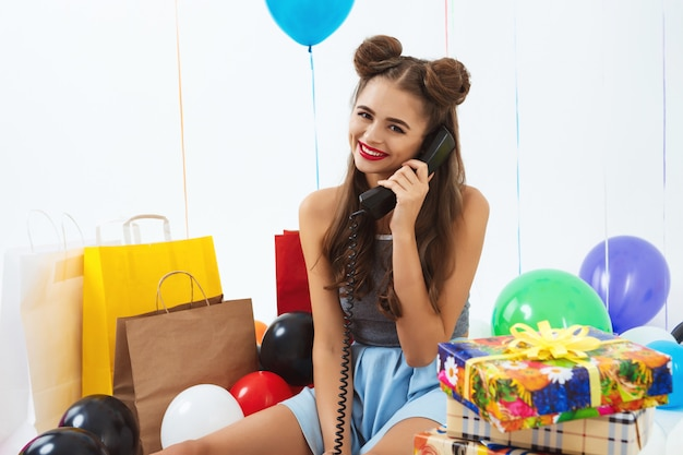 La ragazza adorabile con il fielding operato acconciatura chiama dopo la festa di compleanno