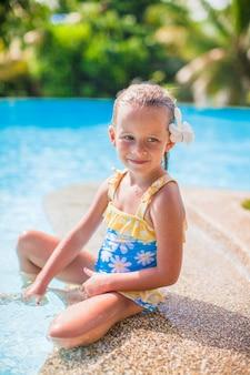 La ragazza adorabile con il fiore dietro il suo orecchio si siede vicino alla piscina