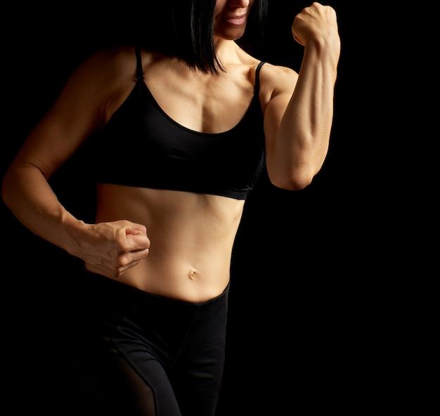 La ragazza adulta con uno sport calcola in reggiseno nero e shorts neri che stanno sul buio