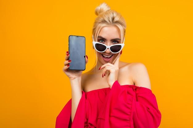 La ragazza affascinante caucasica in un vestito rosso mostra uno schermo in bianco del telefono