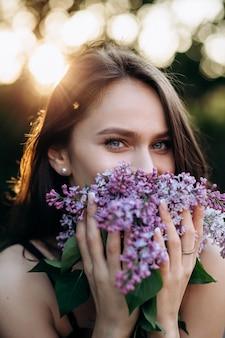 La ragazza affascinante si trova nel parco e mantiene un bouquet
