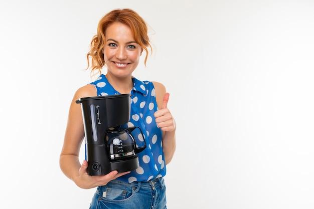 La ragazza affascinante sorride e tiene una macchina del caffè su una parete bianca con lo spazio della copia