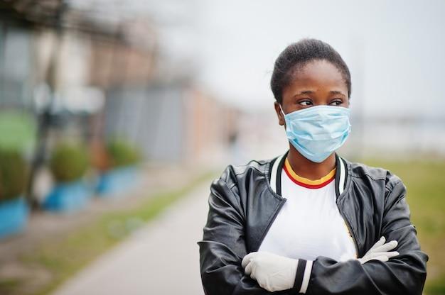 La ragazza africana al parco che indossa maschere mediche protegge da infezioni e malattie da quarantena del virus coronavirus.