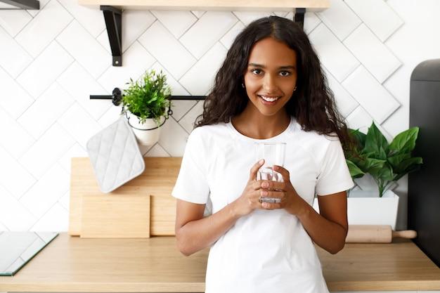 La ragazza africana sta sulla cucina e tiene un bicchiere con acqua