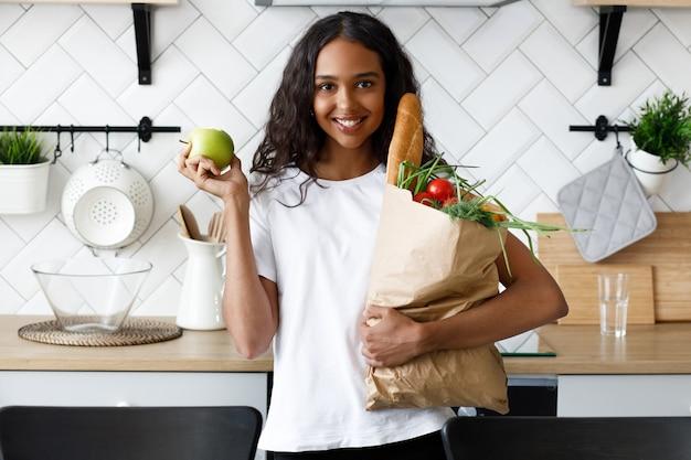 La ragazza africana sta sulla cucina e tiene un sacco di carta con generi alimentari