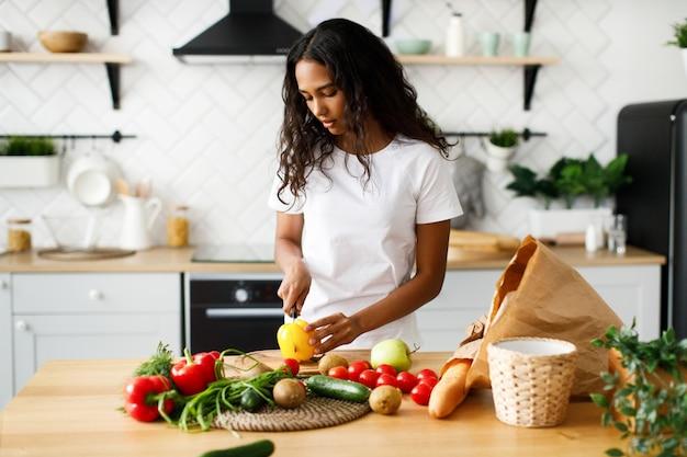 La ragazza africana sta tagliando un peperone giallo sullo scrittorio della cucina e sul tavolo sono i prodotti di un supermercato