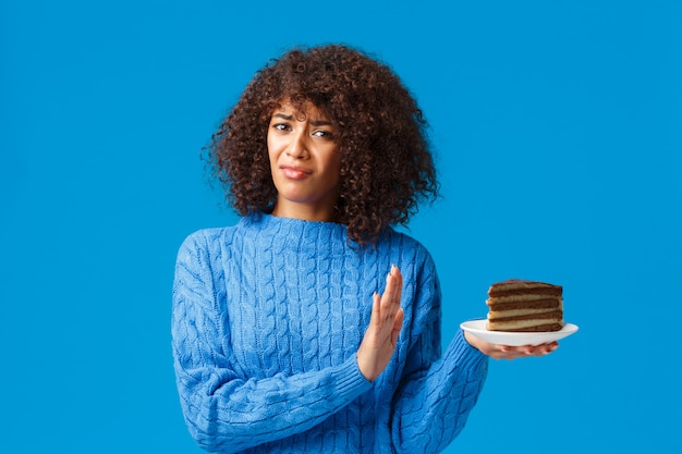 La ragazza afroamericana dispiaciuta e riluttante non ama le cose dolci, tiene la piastra con la torta e fa fermare, il rifiuto o il rifiuto del movimento con la mano, aggrottando le sopracciglia e facendo una smorfia scontenta, antipatia