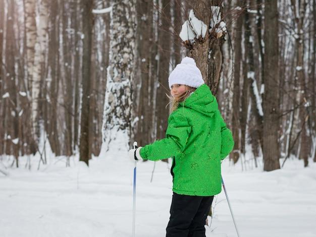 La ragazza al sole nei boschi invernali con gli sci