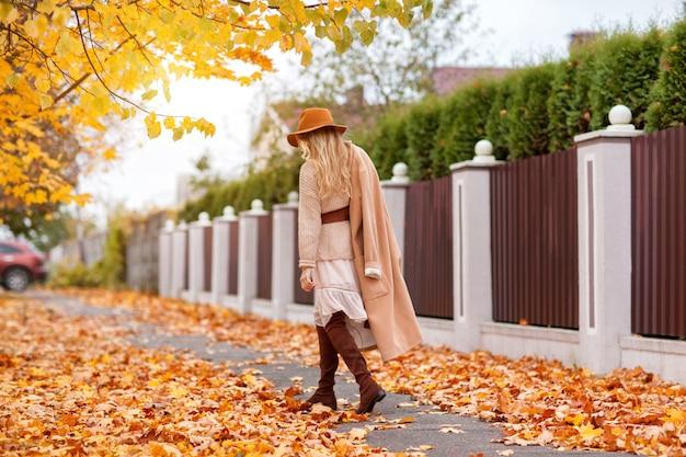 La ragazza alla moda cammina nel parco di autunno in un cappotto e un cappello beige