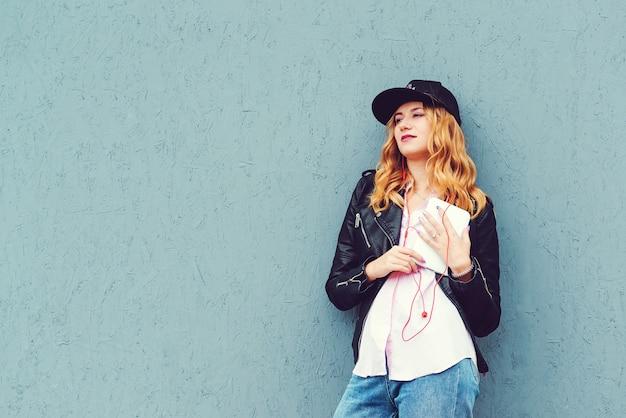 La ragazza alla moda dei pantaloni a vita bassa ascolta musica all'aperto. donna in cuffie e facendo uso della compressa sopra la parete grigia. concetto di moda, tecnologia e persone.