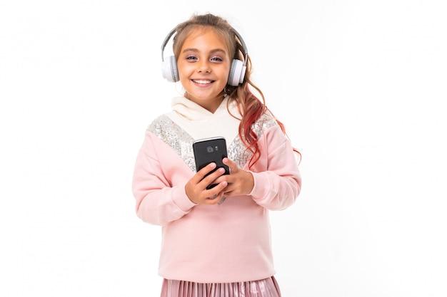 La ragazza alla moda dell'adolescente in felpa con cappuccio rosa gioca nei giochi del telefono