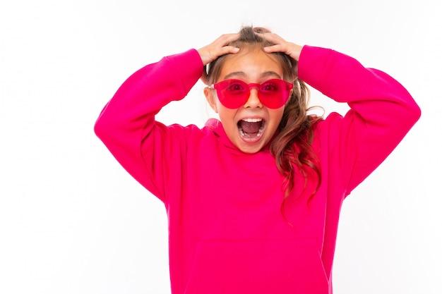 La ragazza alla moda dell'adolescente in maglia con cappuccio rosa e con gli occhiali da sole rosa gesticola sulla parete bianca