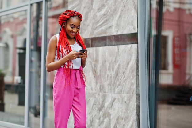 La ragazza alla moda dell'afroamericano ai pantaloni dentellare ed i timori rossi ha proposto all'aperto con il telefono mobile.