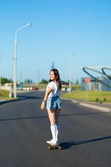 La ragazza alla moda in calze bianche guida sul longboard