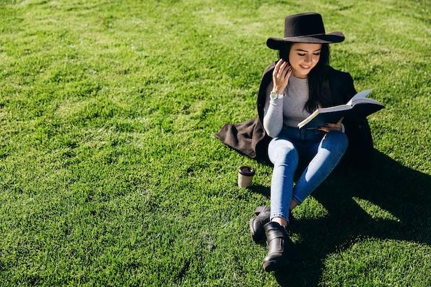 La ragazza alla moda in cappello nero e cappotto si siede con il libro e caffè sul prato prima della biblioteca