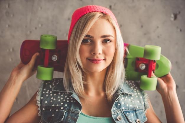 La ragazza alla moda in vestiti di jeans sta tenendo uno skateboard.