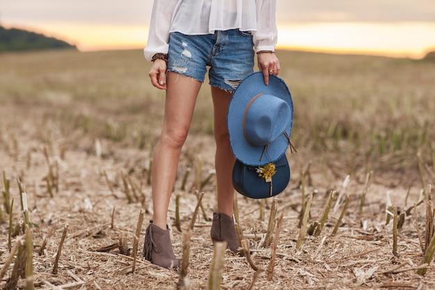 La ragazza alla moda si è vestita nello stile etnico sta in un campo
