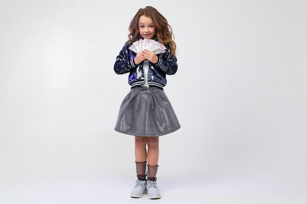 La ragazza alla moda sveglia conta molti soldi con un fan in uno studio con le pareti bianche con spazio
