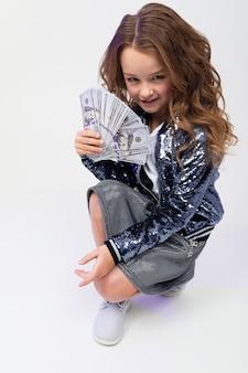 La ragazza alla moda sveglia ha vinto i soldi in un pareggio su una parete bianca
