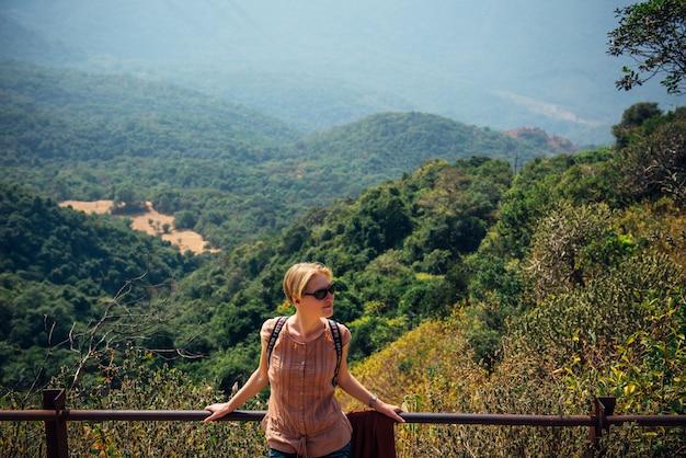 La ragazza alla moda sveglia in occhiali da sole sorride il giorno soleggiato sui precedenti delle colline verdi