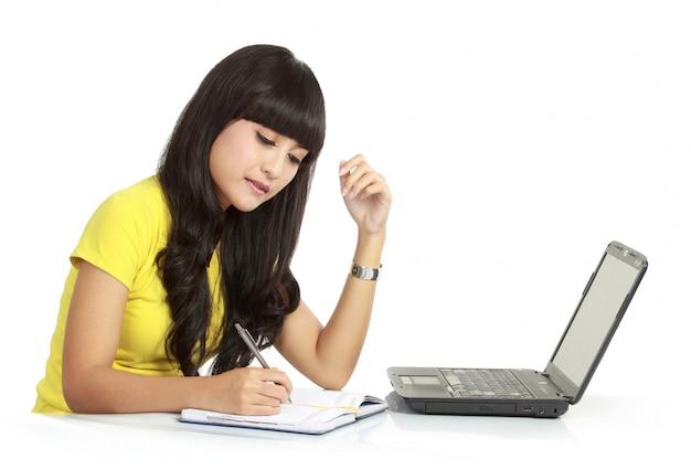La ragazza allegra con il computer portatile e scrive sull'i libri, isolati