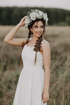La ragazza allegra felice con le trecce e una corona di fiori in un vestito bianco sorride